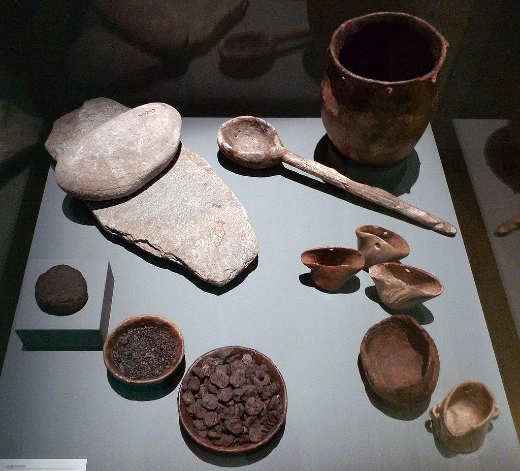 Ausgrabungen der Jungsteinzeit, die in der Schweiz gefunden wurden. Zu sehen sind ein Mahlstein (o.l.), verkohltes Brot (l.), Körner und Apfelstücke (u.) sowie Geschirr (r.)